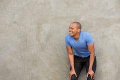 Stilig afrikansk man som ler med händer på knä royaltyfri fotografi