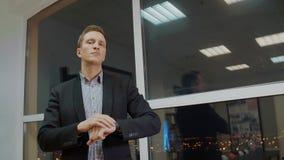 Stilig allvarlig affärsman som i regeringsställning justerar hans armbandsur nära fönster stock video