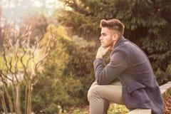 Stilig allvarlig ung man som tänker utomhus Arkivfoto