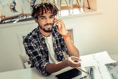 Stilig angenäm svartögd konstnär som talar vid telefonen royaltyfri foto
