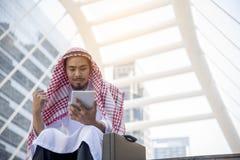 Stilig arabisk man som använder minnestavladatoren, medan sitta i staden Begrepp för affärsframgång royaltyfria bilder