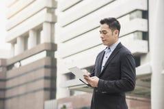 Stilig asiatisk affärsman som använder minnestavlan bruk för bakgrundsbegreppsteknologi arkivfoto