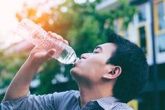 Stilig asiatisk affärsmandricksvattenifrom en flaska Fotografering för Bildbyråer