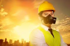Stilig asiatisk arbetare med den skyddande maskeringen och gult hjälmanseende royaltyfria bilder
