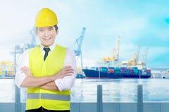 Stilig asiatisk arbetare med gult anseende för hård hatt på kontoret royaltyfri foto