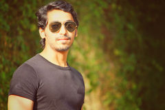 Stilig asiatisk man med solglasögon & att posera för skägg Arkivbild