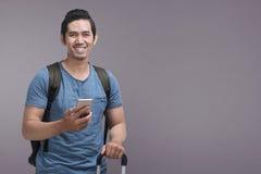 Stilig asiatisk man som använder mobiltelefonen, medan rymma resväskan arkivfoto