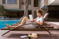 Stilig asiatisk man som kopplar av vid pölen och läs- eBook royaltyfri fotografi