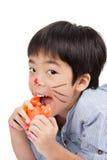 Stilig asiatisk pojke som äter en leksakkrabba royaltyfria bilder