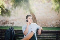 Stilig asiatisk studentman som talar på telefonen, medan sitta på ben Royaltyfria Foton