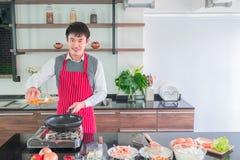Stilig asiatisk ung man i det röda förklädet som ler häller olja på pannan för för att förbereda mat royaltyfria foton