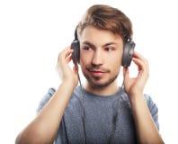 Stilig bärande hörlurar för ung man och le, medan stå arkivbild