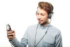 Stilig bärande hörlurar för ung man och lyssna till musik arkivfoton
