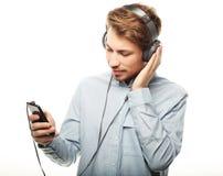 Stilig bärande hörlurar för ung man och lyssna till musik royaltyfri bild
