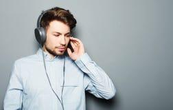 Stilig bärande hörlurar för ung man och lyssna till musik fotografering för bildbyråer