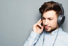 Stilig bärande hörlurar för ung man och lyssna till musik arkivfoto