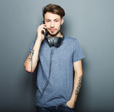Stilig bärande hörlurar för ung man på hans hals och lewh royaltyfria foton