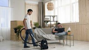 Stilig bögdans och rengöring med portionen av dammsugaren medan hans partner som talar på telefonen och använda stock video