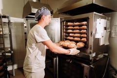 Stilig bagare i det enhetliga hållande magasinet som är fullt av nytt bakat bröd på tillverkningen Royaltyfri Bild