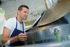 Stilig bagare som kontrollerar ugnen på tillverkning arkivfoto