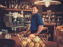 Stilig bartender som har gyckel på stångräknaren i bageri fotografering för bildbyråer