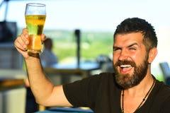 Stilig bartender som rymmer en halv liter av ?l Mannen rymmer exponeringsglas av ?l Tyck om i bar ?ltid arkivbild