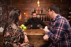 Stilig bartender som talar med kunder på stångräknaren i en bar royaltyfria bilder