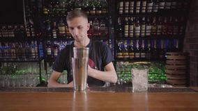 Stilig bartendermixologist som sätter många kuber av isar i exponeringsglas och går att göra coctailen i härlig modern stång lager videofilmer