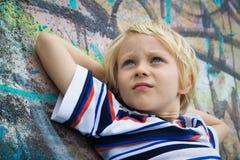 Stilig bekymrad pojke som tänker mot grafittiväggen royaltyfri fotografi