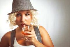 Stilig blond kvinna i hatt som dricker konjak, affärsstil Arkivbild