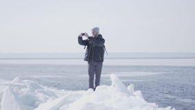 Stilig blond skäggig man i exponeringsglas i varmt vinteromslagsanseende på iskvarteret på glaciären som tar på fotoet stock video