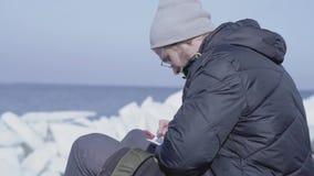 Stilig blond skäggig man som sitter bland isarna som skriver hans observationer i en anteckningsbok Polar utforskare på glaciären arkivfilmer