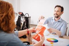 Stilig bra seende man som hjälper hans kollega att välja färgen Fotografering för Bildbyråer