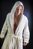 Stilig bärande vit badrock för ung man Arkivbild