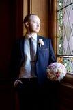 Stilig brudgum i dräkt i korridoren Fotografering för Bildbyråer