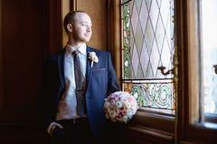 Stilig brudgum i dräkt i korridoren Royaltyfri Bild