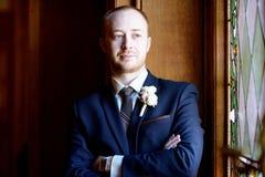 Stilig brudgum i dräkt i korridoren Royaltyfri Foto