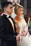 Stilig brudgum i dräkt och en hållande cand för härlig blond brud Arkivfoton