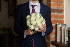 Stilig brudgum i hållande vit b för stilfull svart dräkt och för rött band royaltyfria bilder