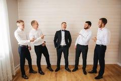 Stilig brudgum med hans groomsman hemma Man fem Iklädd dräkt för brudgum, gromsmen i den vita skjortan Roliga grabbar på arkivbilder