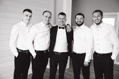 Stilig brudgum med hans groomsman hemma Man fem Iklädd dräkt för brudgum, gromsmen i den vita skjortan Roliga grabbar på royaltyfri bild