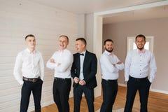 Stilig brudgum med hans groomsman hemma Man fem Iklädd dräkt för brudgum, gromsmen i den vita skjortan Roliga grabbar på arkivfoto