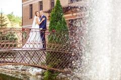 Stilig brudgum och attraktiv brud som kramar, medan stå på br arkivbilder