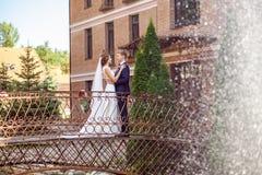 Stilig brudgum och attraktiv brud som kramar, medan stå på br arkivfoton