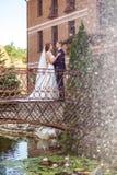 Stilig brudgum och attraktiv brud som kramar, medan stå på br arkivbild