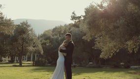 Stilig brudgum som kramar hans fantastiska brud medan stock video