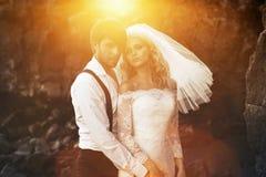 Stilig brudgum som kramar hans härliga fru Royaltyfria Bilder