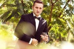 Stilig brudgumbröllopdag som ler och dricker vin eller champagne Royaltyfri Fotografi