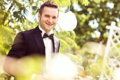 Stilig brudgumbröllopdag som ler och dricker vin eller champagne Arkivbild