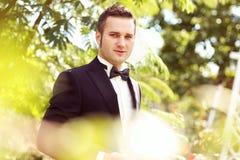 Stilig brudgumbröllopdag som ler och dricker vin eller champagne Royaltyfria Bilder